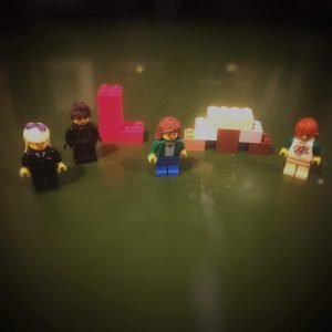 four lego minifigs and letters LM made of lego bricks